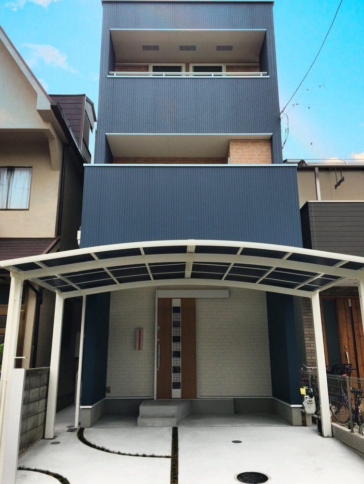 青い外壁が目を引く3階建ての2世帯住宅